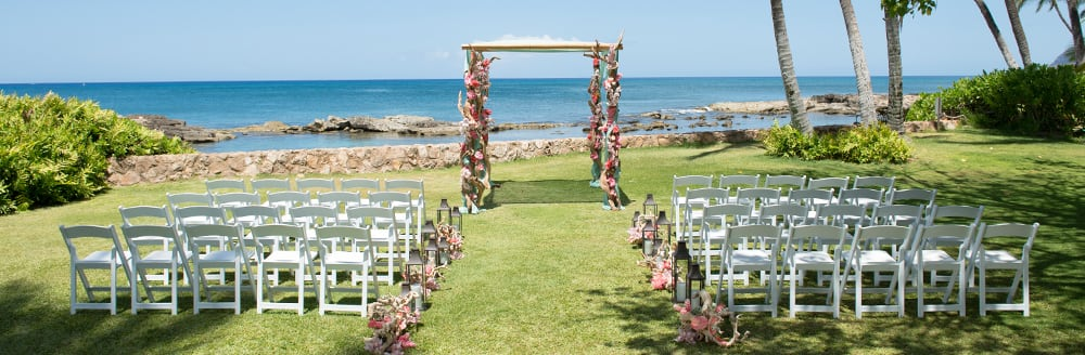 Folding chairs on both sides of an aisle leading towards an altar on a lawn by the ocean