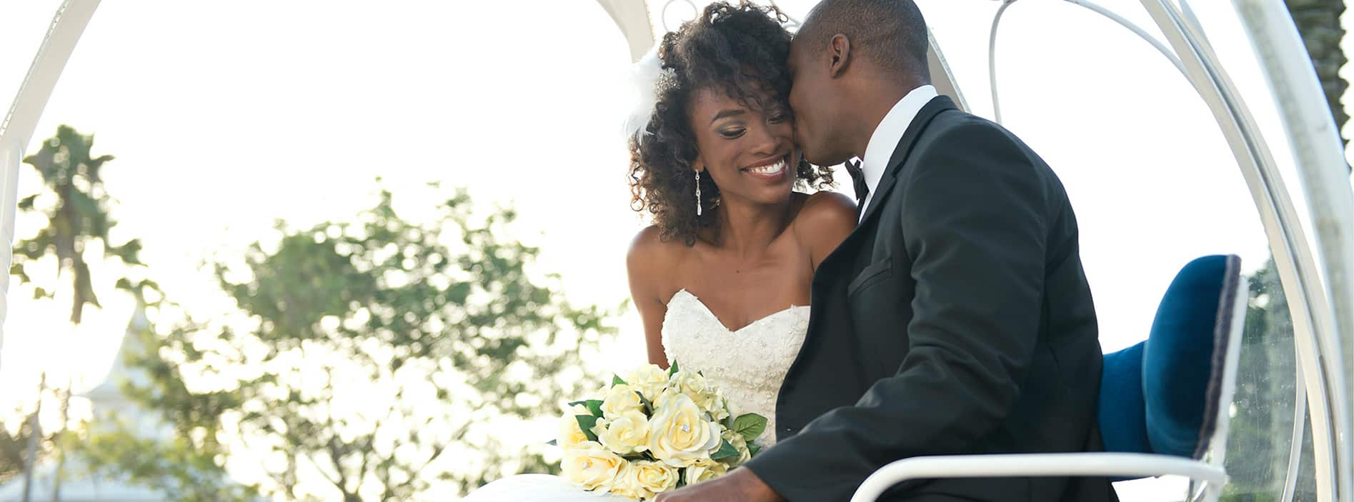 Couple riding on Cinderella Coach and smiling at each other on wedding day