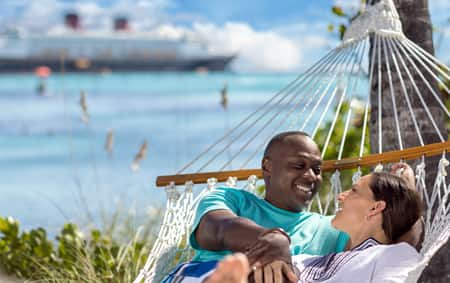 A man and a woman lie in a hammock next to an ocean, looking at each other lovingly