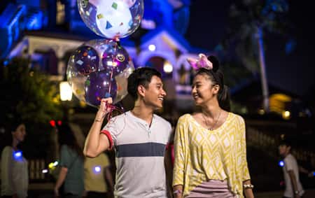 A man and a woman share smiles in front of Mystic Manor after nightfall