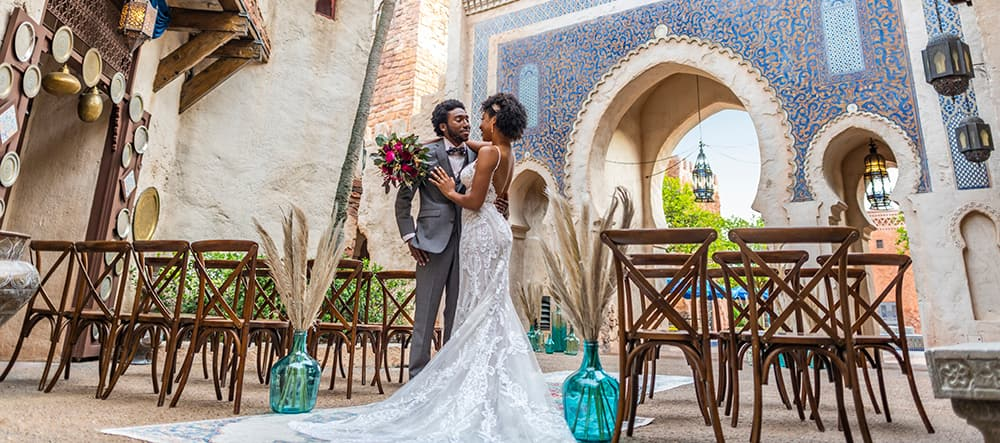 A bride and groom stand amid empty chairs and gaze into each other's eyes in the EPCOT Morocco Pavilion at Walt Disney World Resort