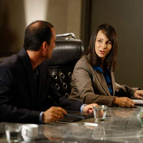 A women and a man in business attire seated at a conference room table and conversing