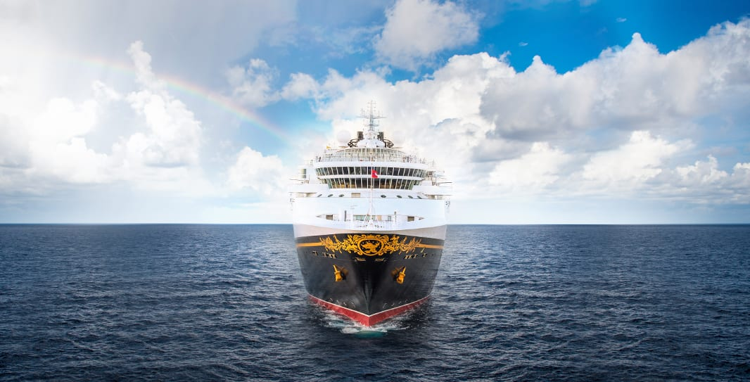 A Disney Cruise line ship sails on calm seas with a partly cloudy sky and a rainbow behind it