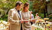 A man and a woman each hold plates with food as they walk along a buffet line