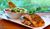 A plate with a salmon filet, red potatoes and a salad with garlic bread