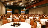 A ballroom with round tables and seating for hundreds of Guests, and a stage with twin video panels