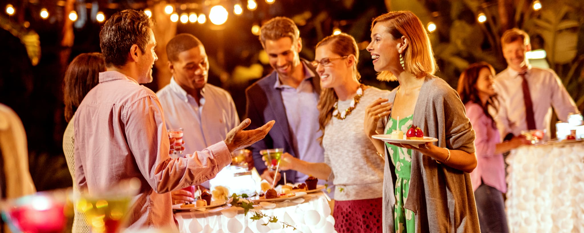 Smiling people standing around high tables draped with linens featuring dessert plates and beverages in an outdoor setting