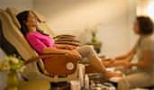 A Guest in a spa chair gets a pedicure and a leg massage