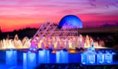 A smiling chef standing behind an illuminated food station at sunset near an active fountain with Spaceship Earth at Epcot in the distance