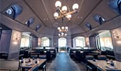 A dining room with three chandeliers hanging from the ceiling and a mix of booths and tables set for service at Ale and Compass Restaurant in Disney's Yacht Club Resort