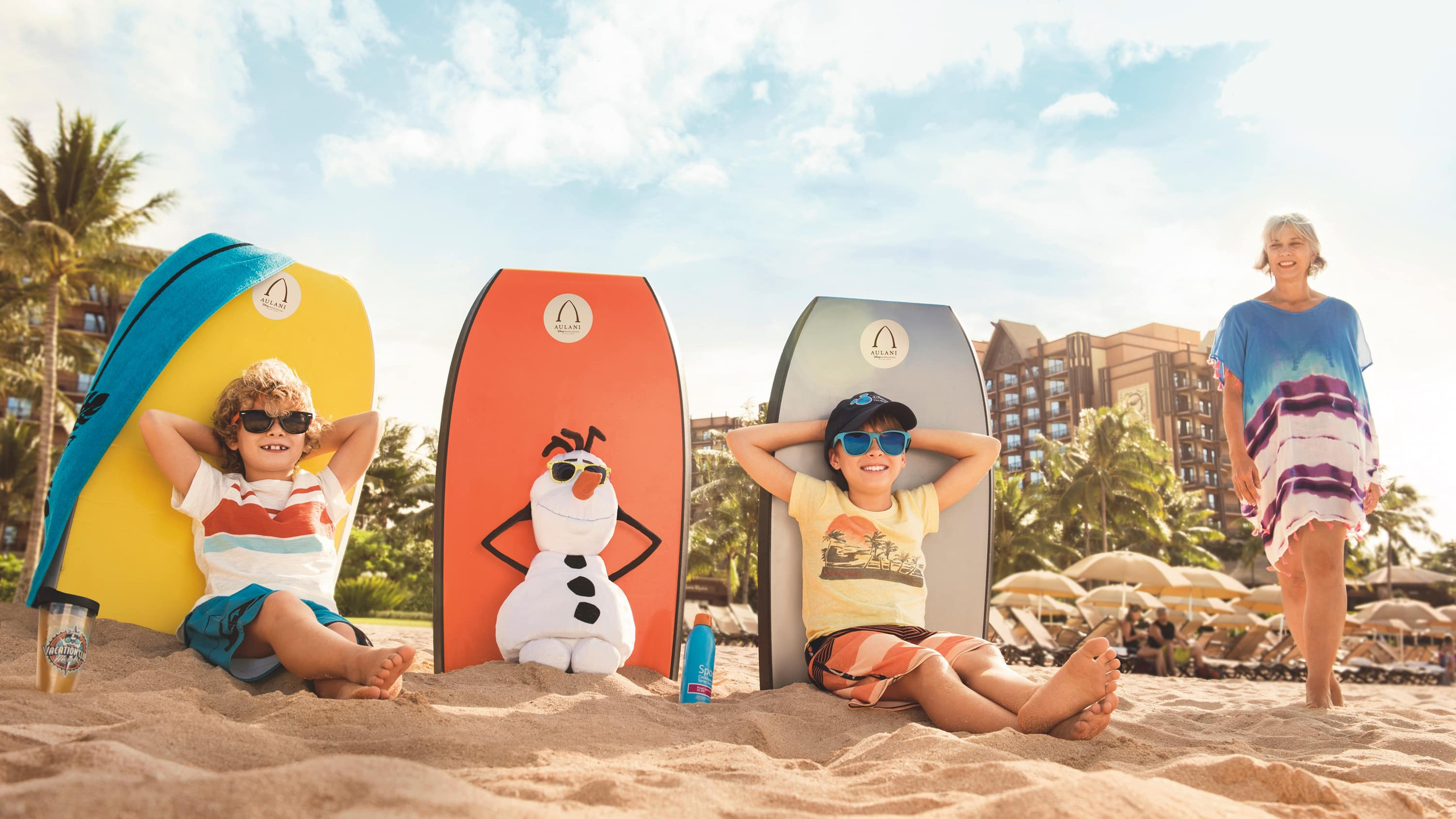 Two boys sit on the beach with Olaf the snowman, while their grandmother stands nearby
