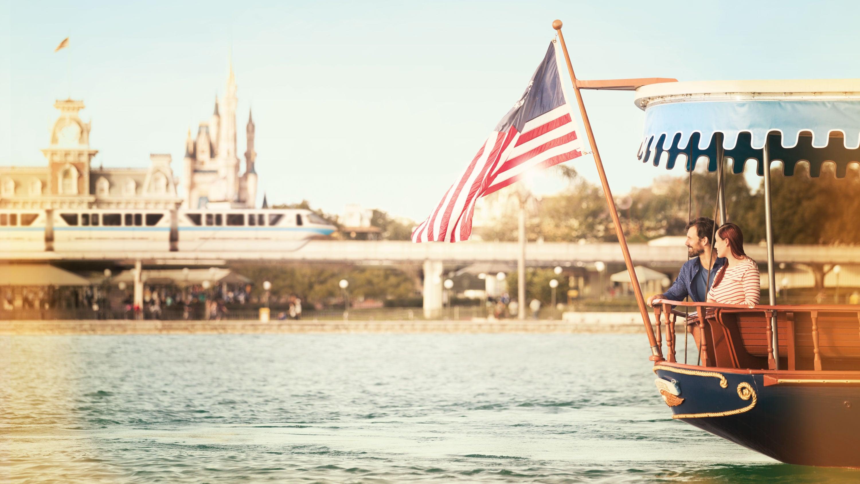 アメリカの国旗を掲げたフェリーに乗ってマジックキングダム・パークの前を通り過ぎるカップル