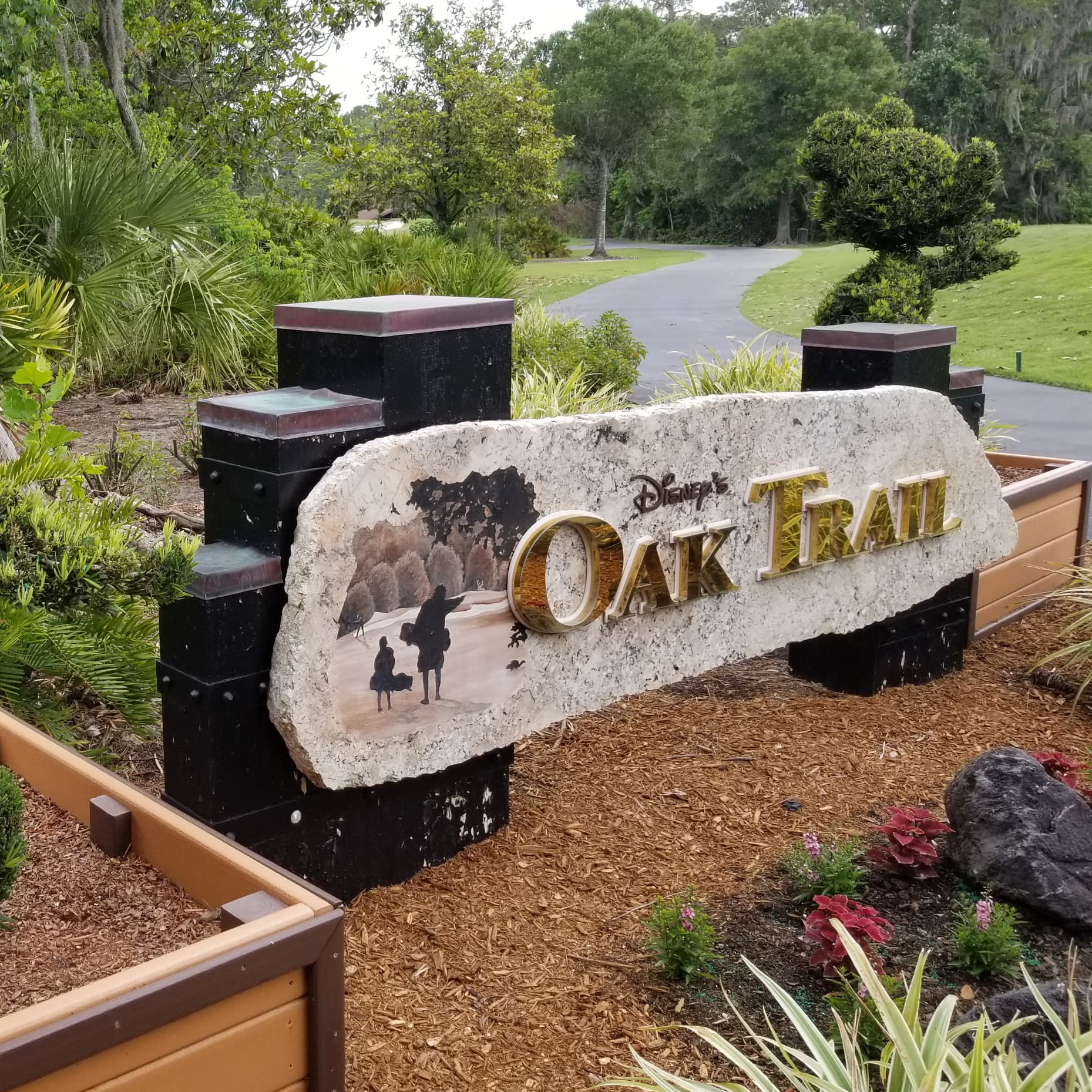 A sign that reads 'Disney's Oak Trail' located beside a golf cart path