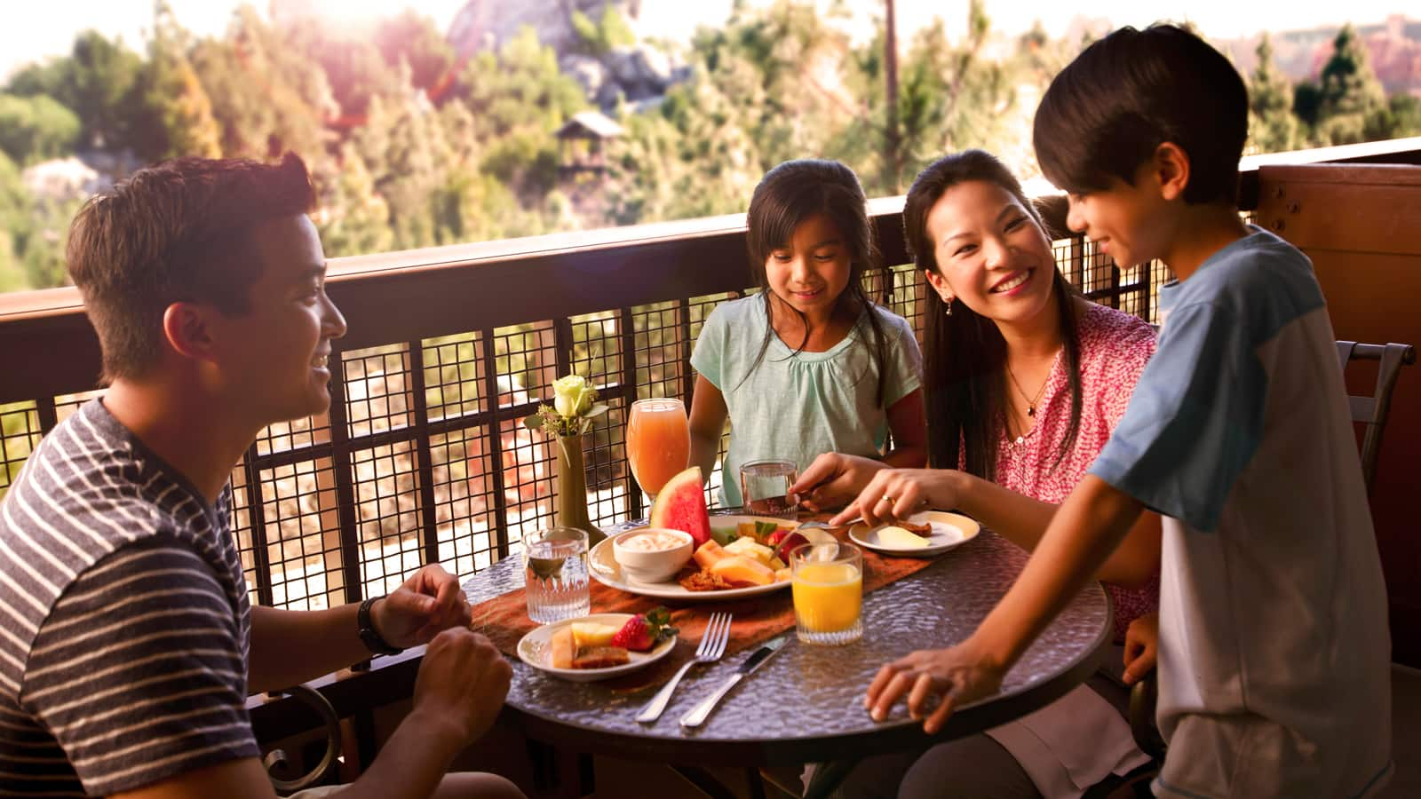 A family of 4 gather around a table with breakfast food on an outdoor balcony