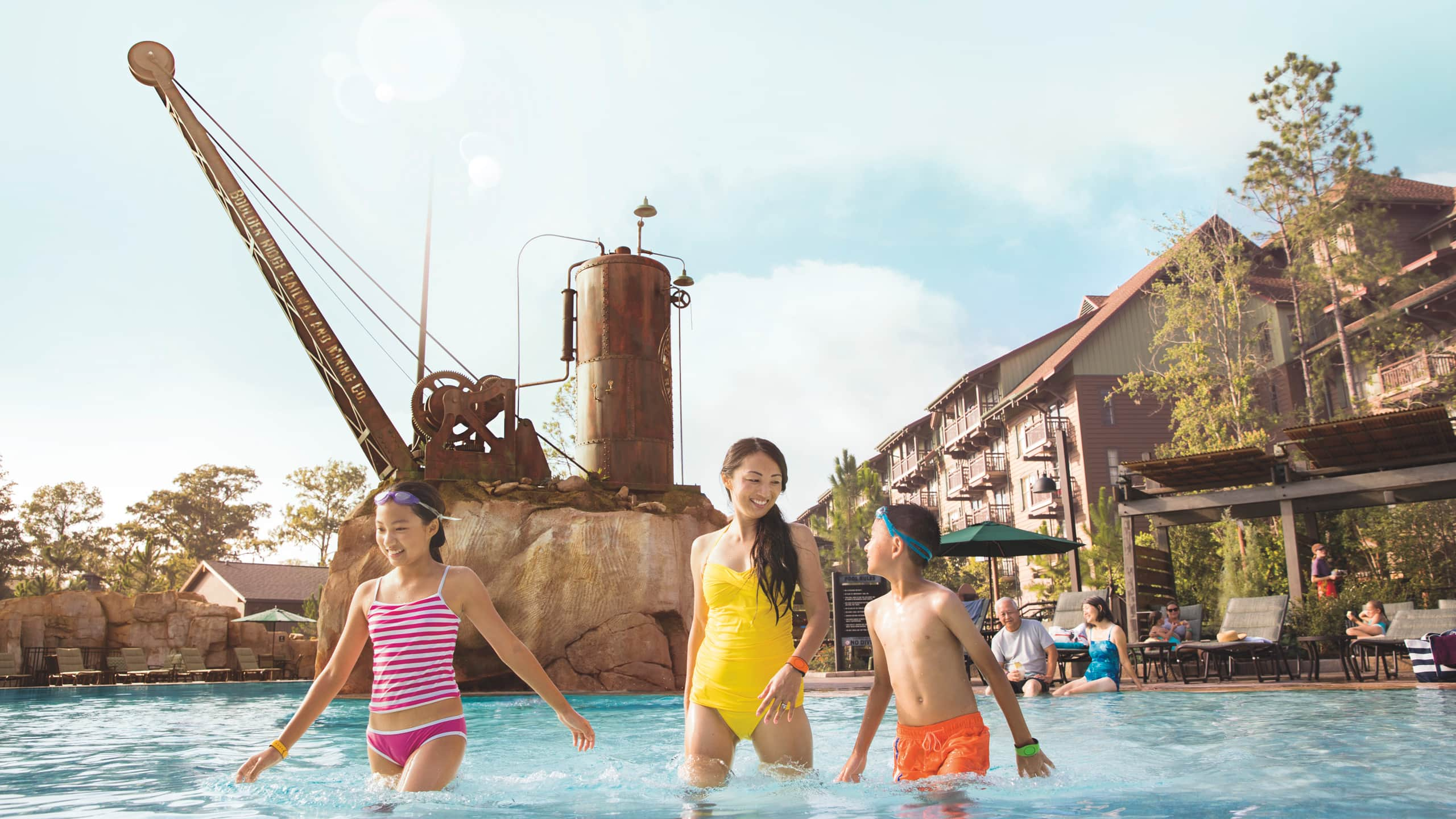 A woman and 2 children wade in a pool in front of a hotel themed in a rustic setting