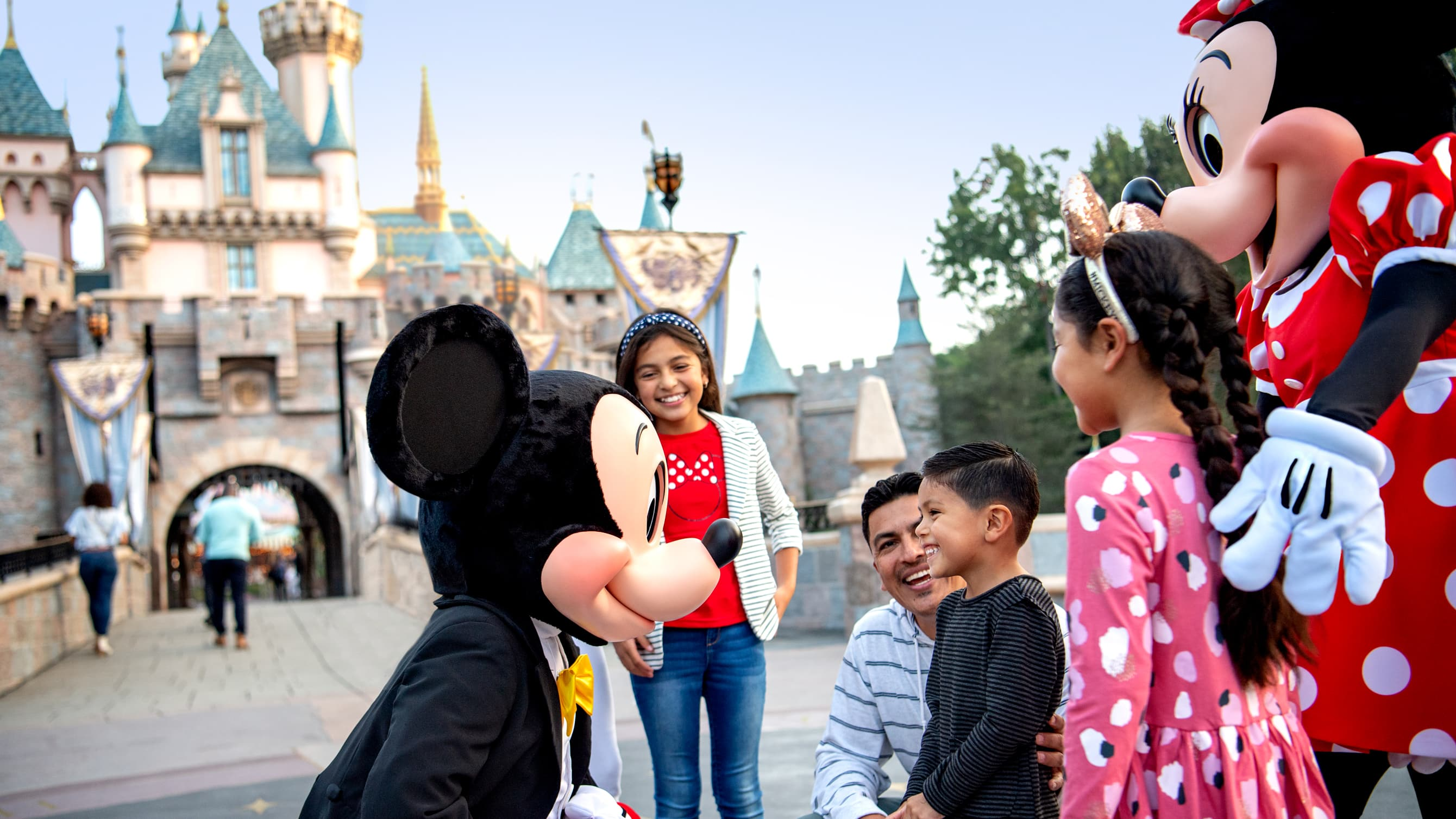 Mickey and Minnie Mouse greet a boy standing with his 2 sisters and his father