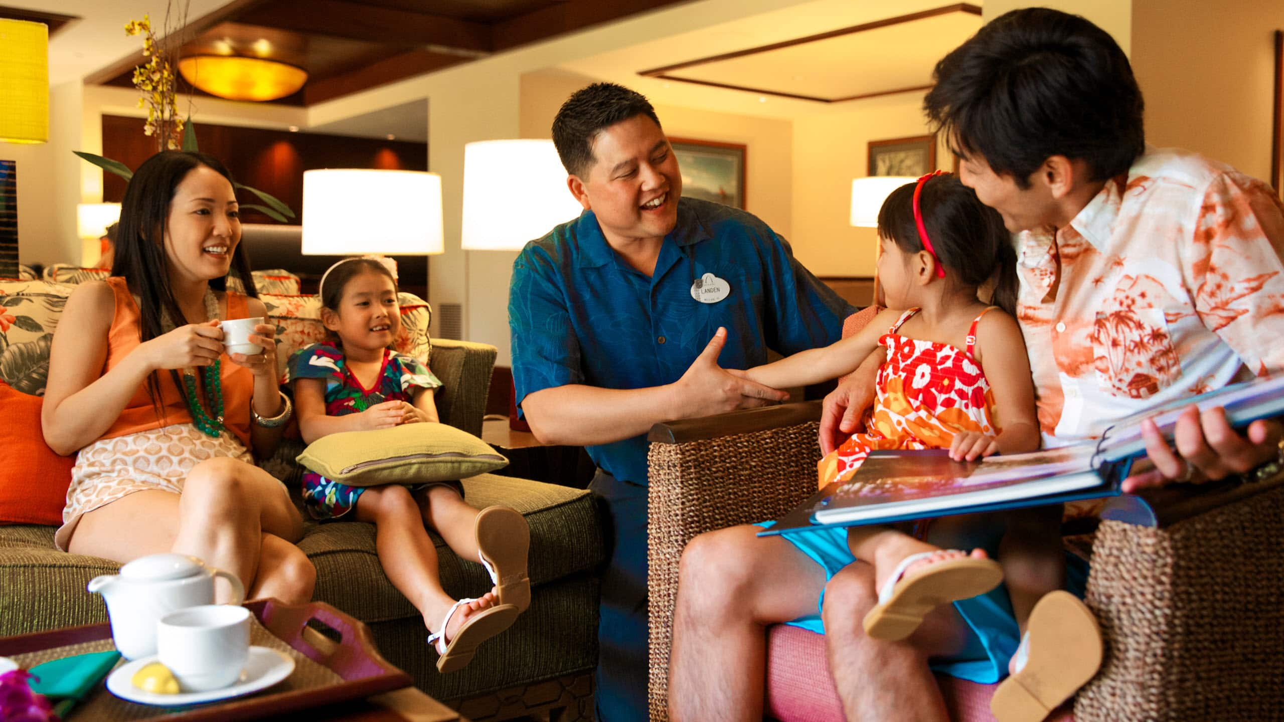 A Disney Cast Member greets a family of 4 in a lounge area