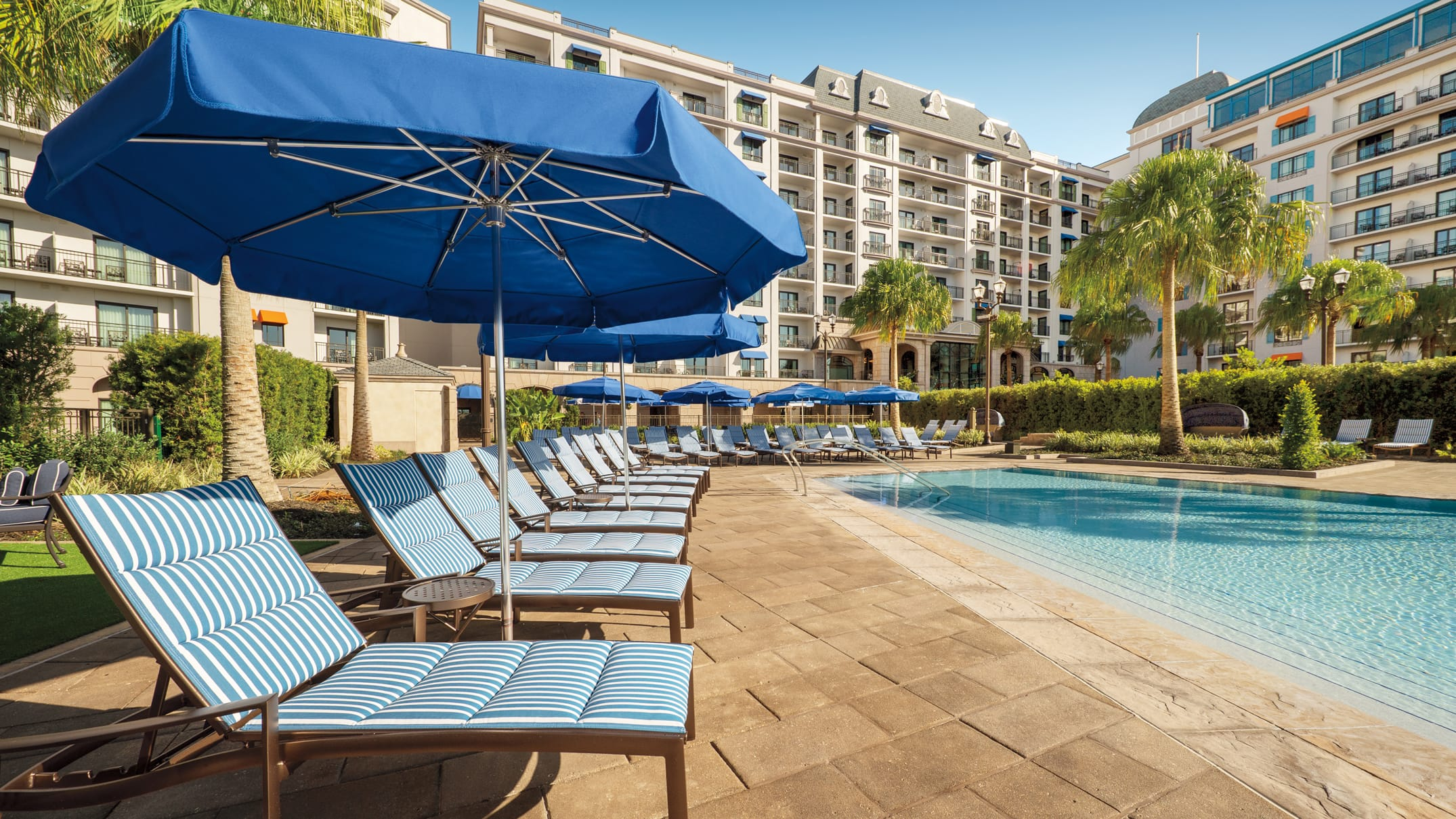 Several chaise lounge chairs and sun umbrellas surrounding Beau Soleil Pool at Disney's Riviera Resort