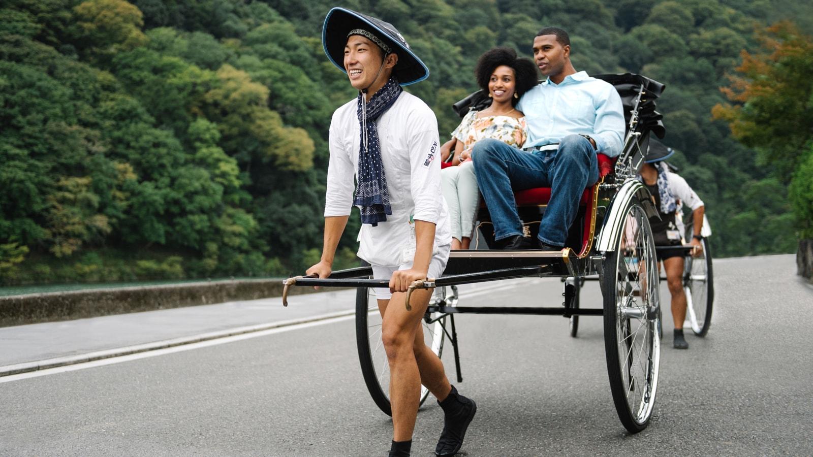 A man and woman riding in a rickshaw cart near a mountain