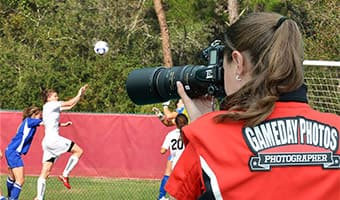 A GameDay Photos photographer snaps a picture of girls playing soccer