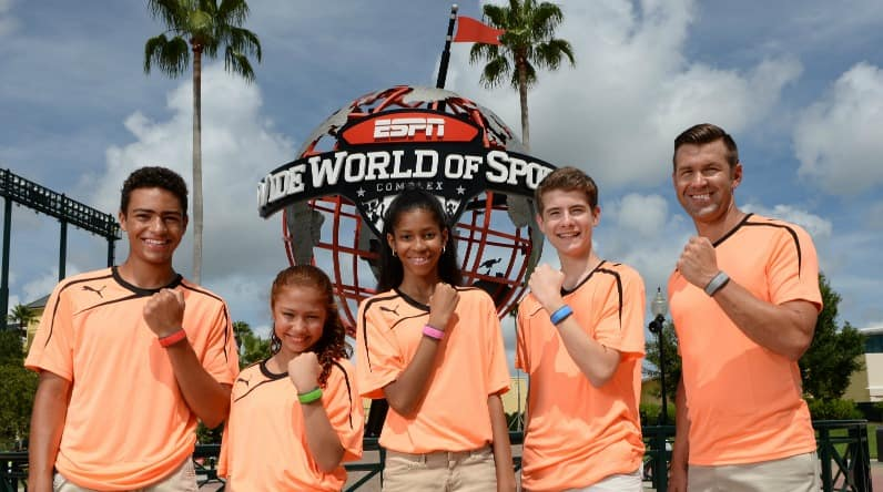 A group of people in matching shirts show off their Magic Bands at ESPN Wide World of Sports Complex
