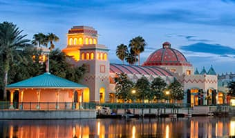Spanish colonial buildings of Disney's Coronado Springs Resort on the edge of Lago Dorado at night