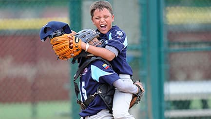 A baseball catcher hugging his teammate