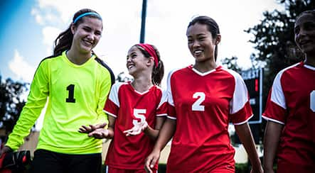Four girl soccer players laughing on a field