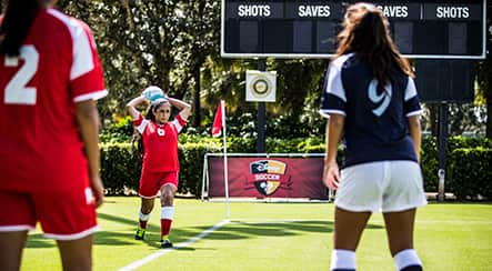 A teenage girl soccer player throwing a ball into play