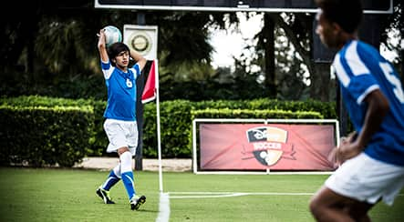 A teenage boy soccer player throwing a ball into play