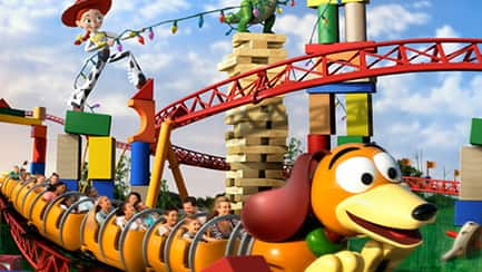 The Slinky Dog Dash roller coaster careens past Jessie and Rex, who are standing atop building blocks holding a string of holiday lights
