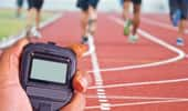 Hand holding a stopwatch with runners in the background