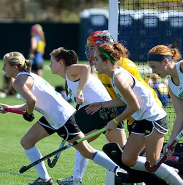 A field hockey player tries to control a ball while her opponent attempts to steal it