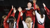 A team of young female gymnasts celebrate with a group high-five