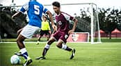 On a soccer field, a player dribbles a ball as a defender guards him and a goalie defends the goal