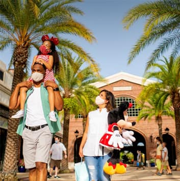 Family wearing masks walking through Disney Springs with a mom holding a Minnie Mouse plush figure.