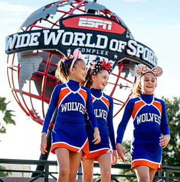 Three young cheerleaders in matching uniforms with 'Wolves' on the top walk near a large globe with a logo that reads 'ESPN Wide World of Sports Complex'