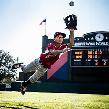 A youth baseball player dives for a baseball in the outfield near a scoreboard that reads 'ESPN Wide World of Sports'