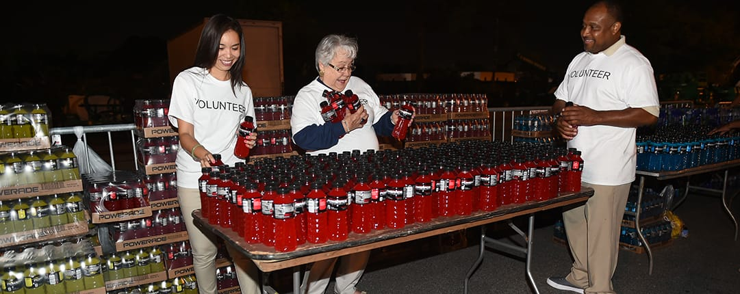 While preparing for the race, volunteers fill a table with bottles of Powerade taken from stacks of cases behind them