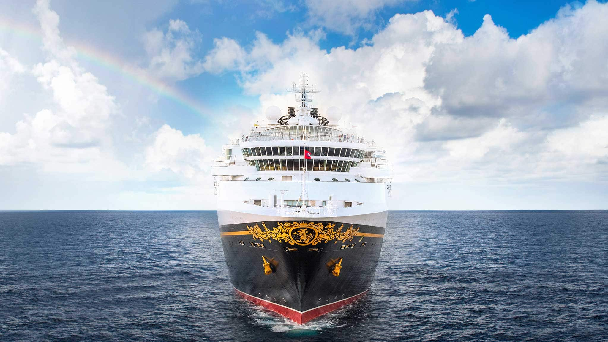 A Disney Cruise Ship Cuts Through The Ocean With Clouds And A Rainbow In The Sky