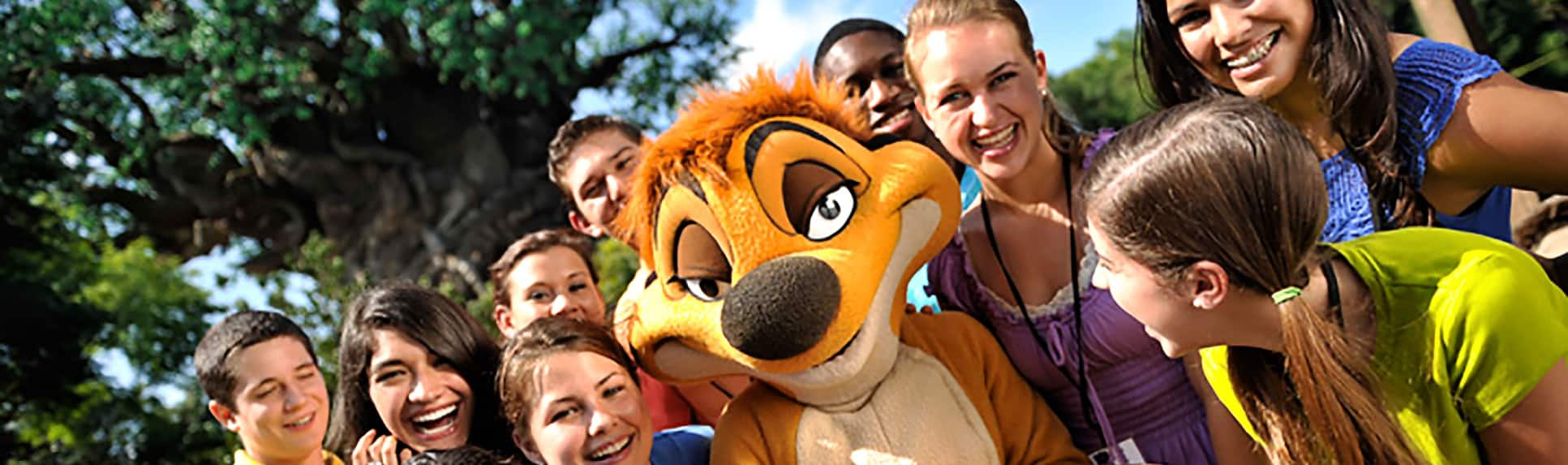 Young adults smile next to the Timon Character