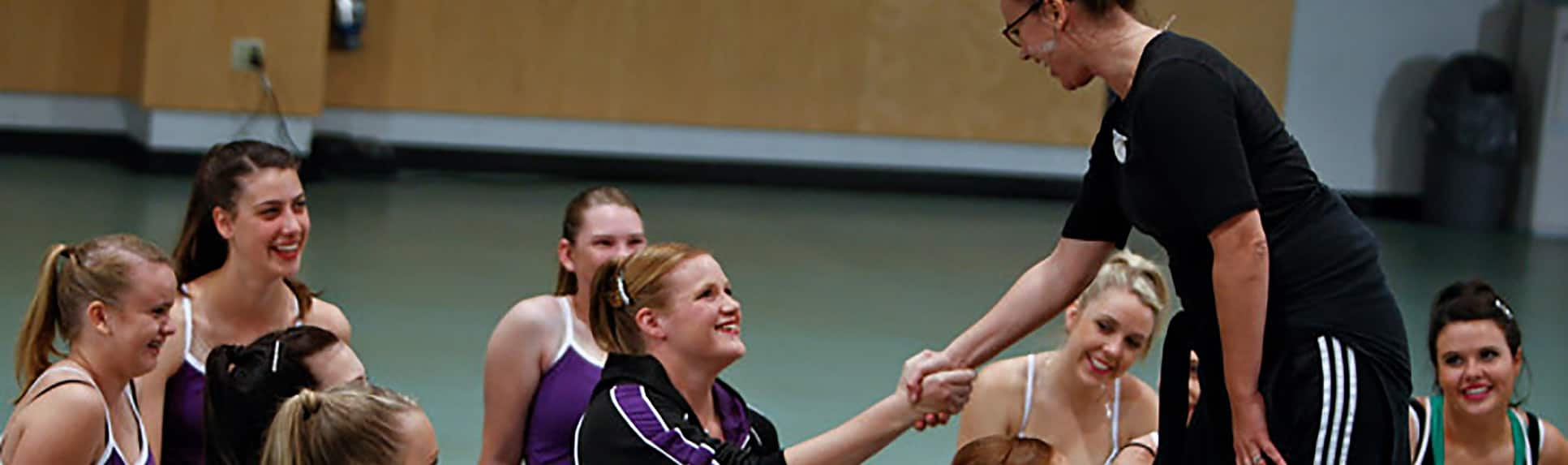 An adult shaking hands with a young woman in a room of smiling  dancers wearing uniforms and jazz shoes