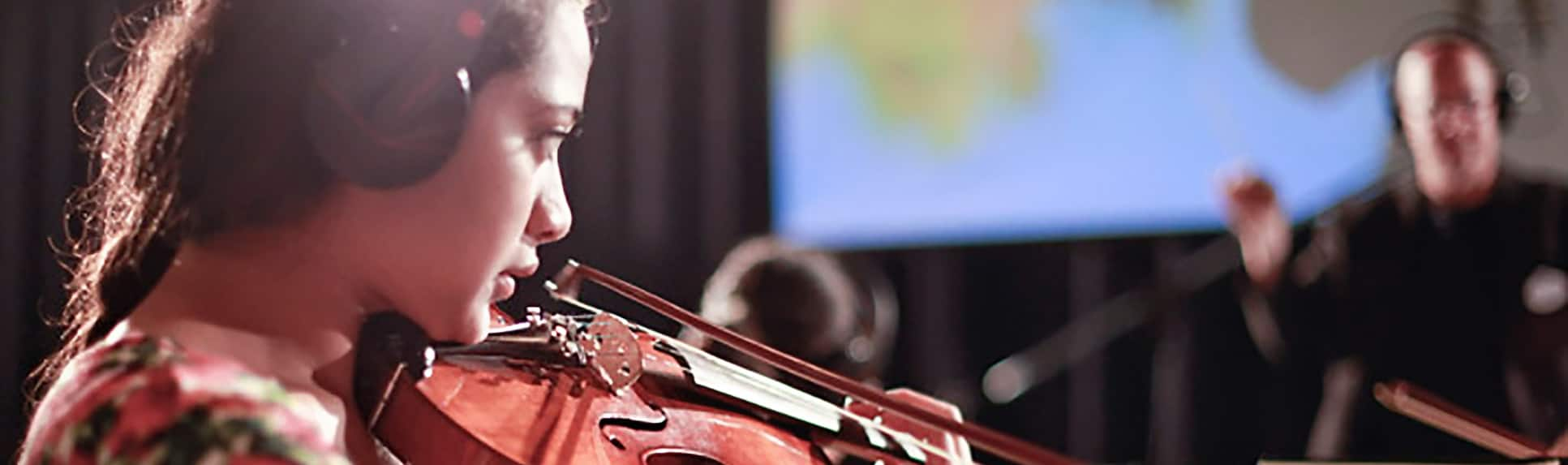 A young girl wearing headphones playing the violin