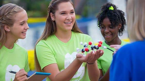 A young adult holds a notepad and pen next to another young lady who holds a chemistry molecular model