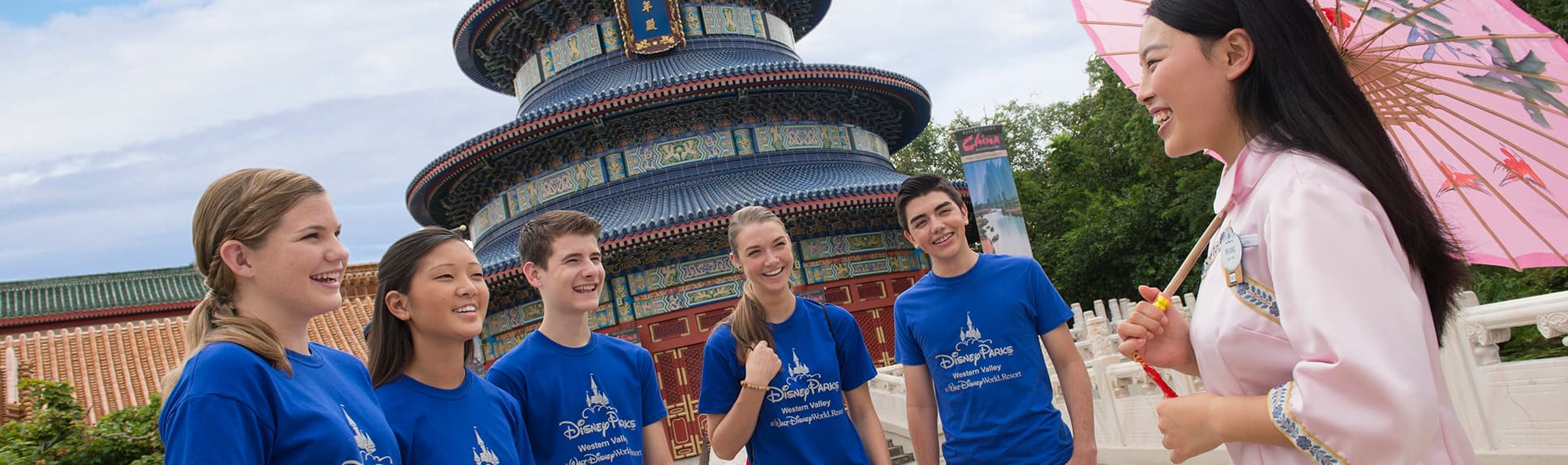 Young adults smiling with a Cast Member near the Temple of Heaven at Epcot