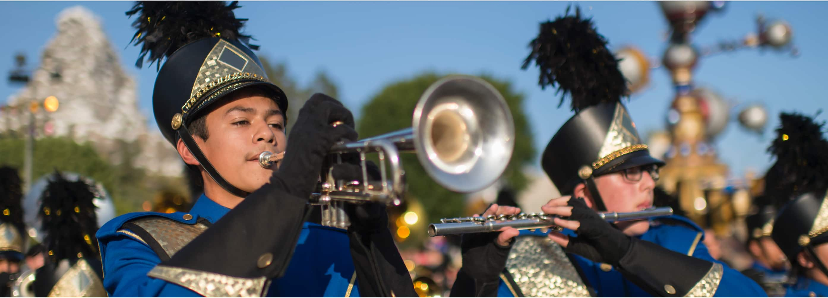 A boy playing a trumpet and a girl playing a flute perform in a high school marching band
