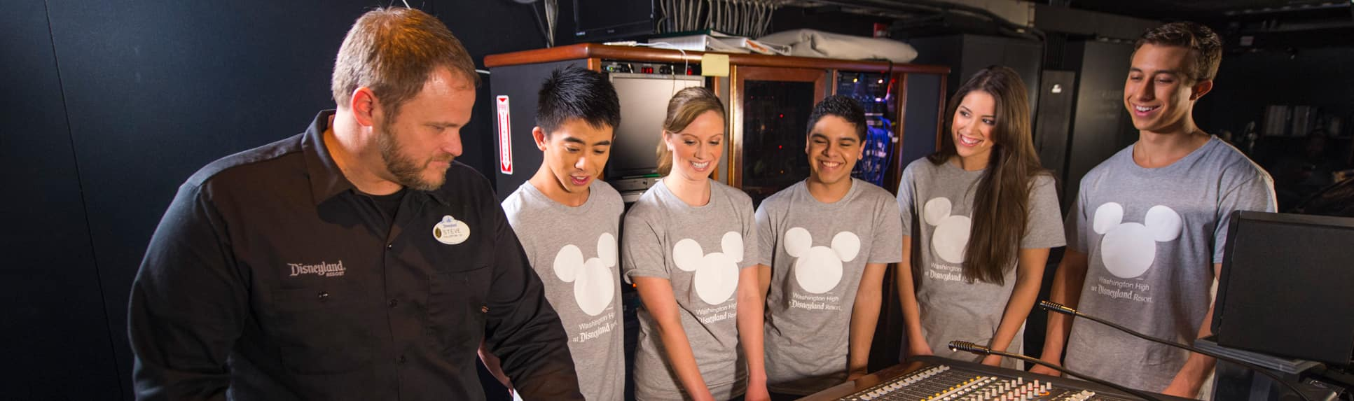 A Cast Member showing a group of teenagers around an audio control booth