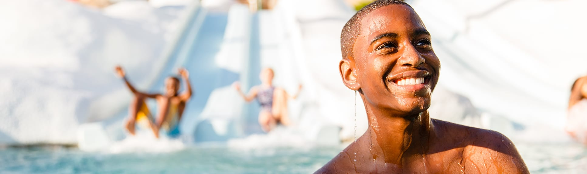 A smiling Guest in a pool by a water slide