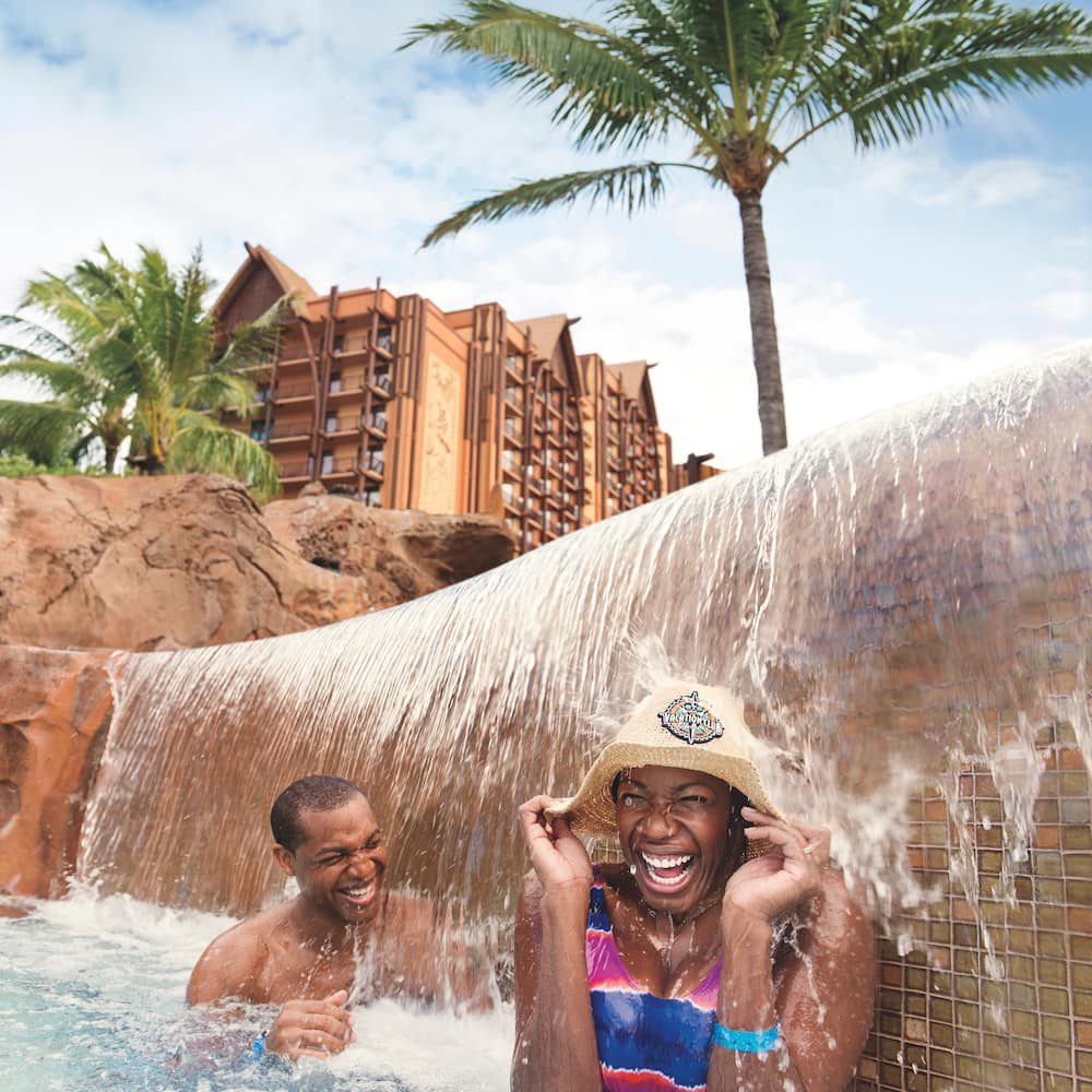 A man and a woman holding onto her hat are all smiles as they stand under a waterfall at an Aulani Resort pool