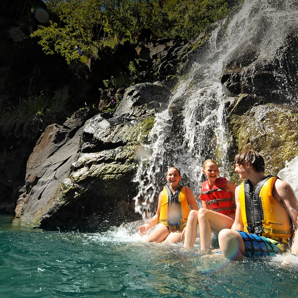Three kids with lifejackets, sitting at the base of a waterfall